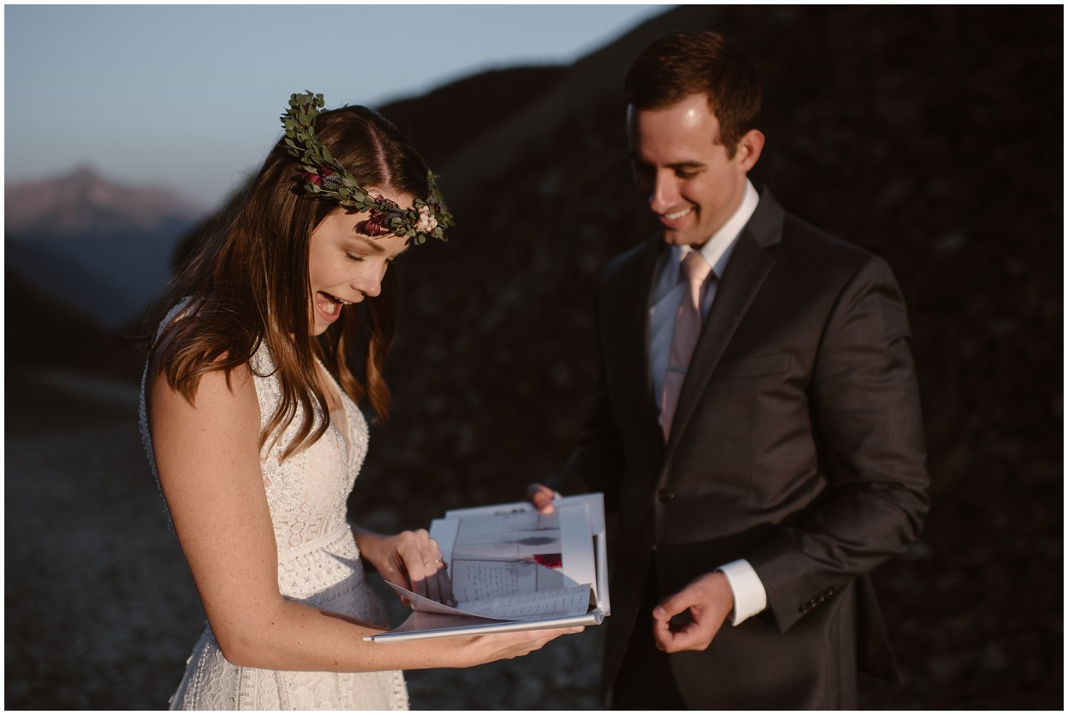 A bride and groom smile as they open a folder of letters from family and friends.