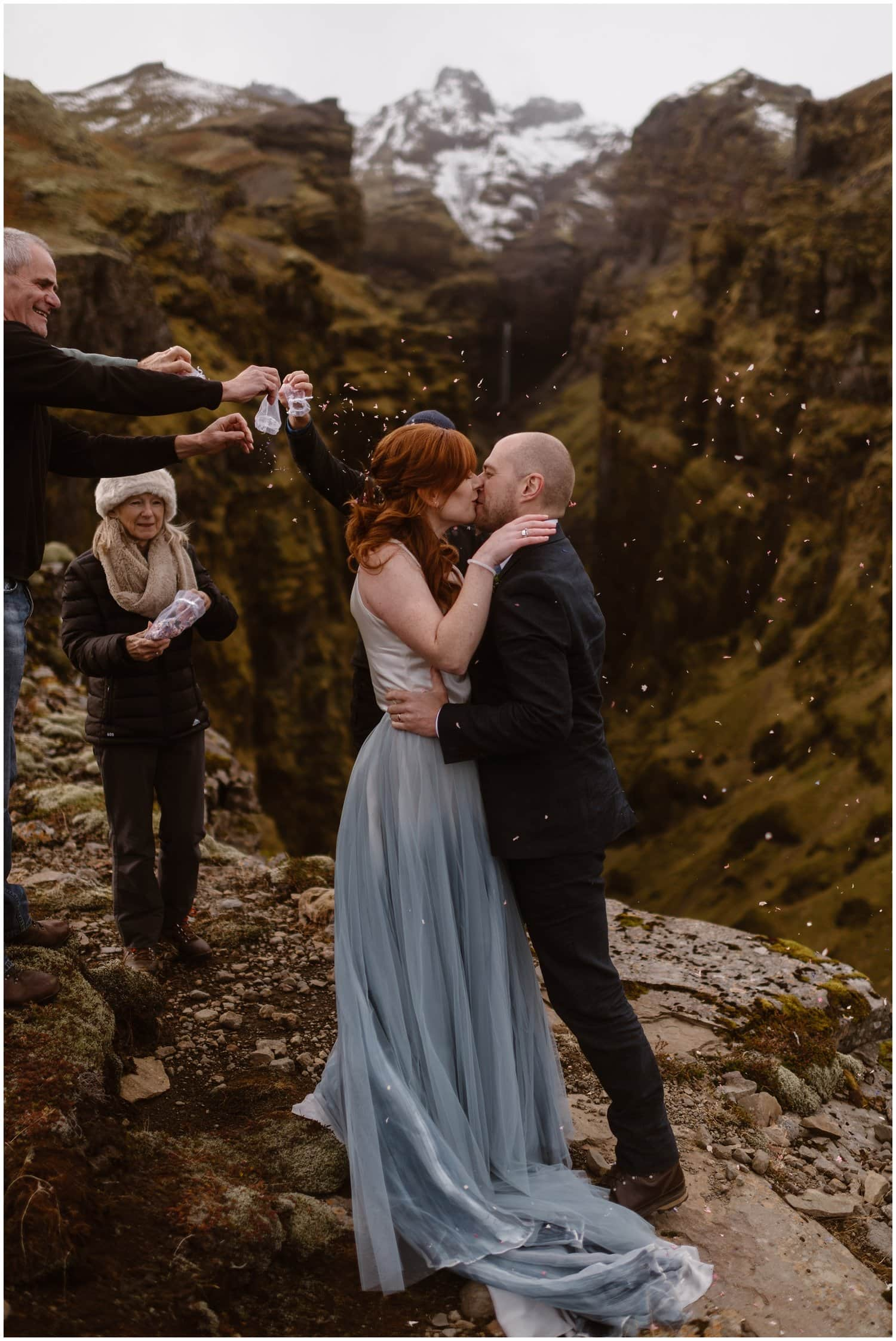 Bride and groom kiss during their elopement ceremony while family and friends throw confetti.