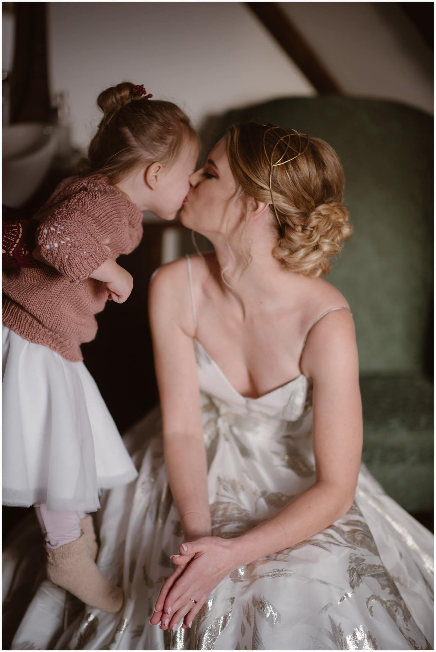 Bride kisses her little girl on her wedding day.