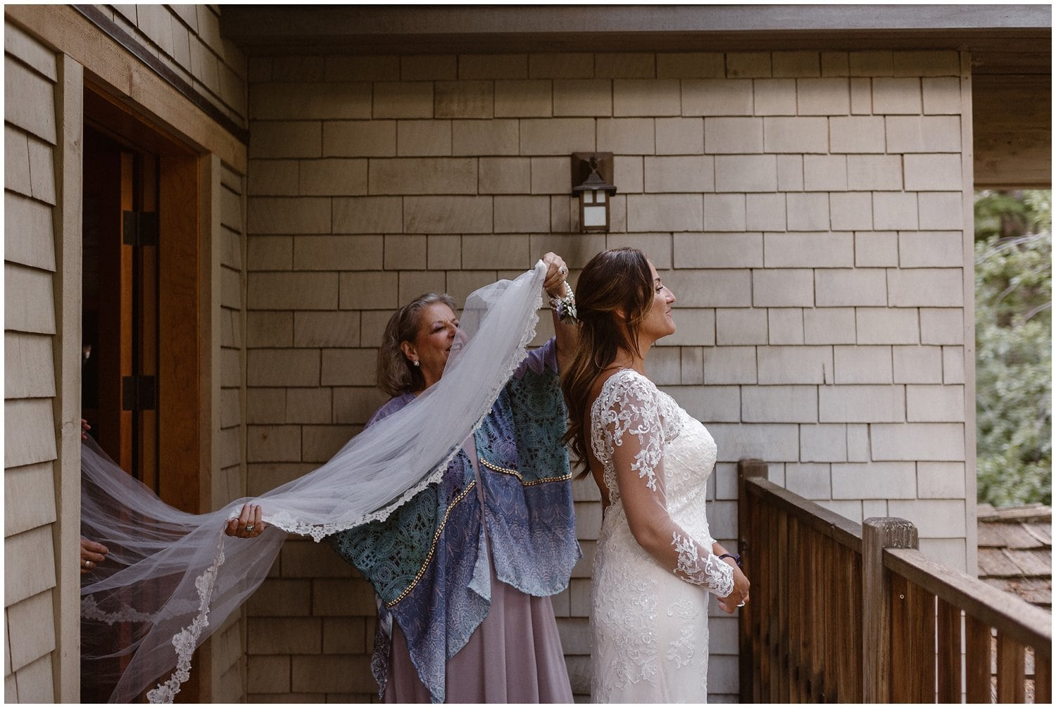 A bride stands on a balcony while a woman helps put on her wedding veil.