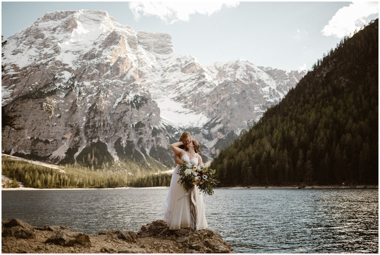 Two women embrace at the lake during their mountain elopement.