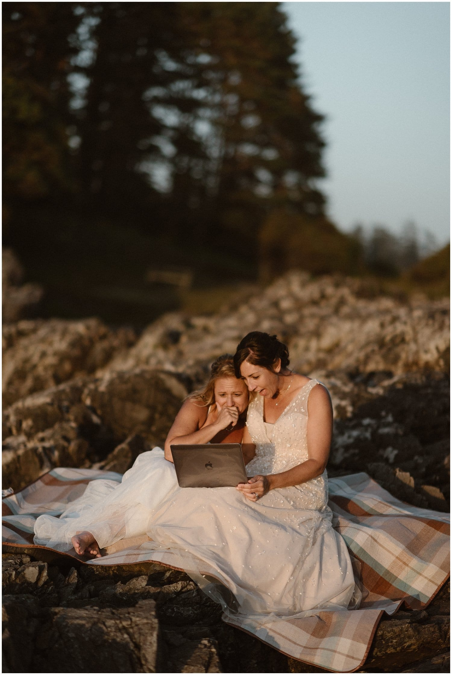 Two brides smile while looking at a computer on a picnic blanket.