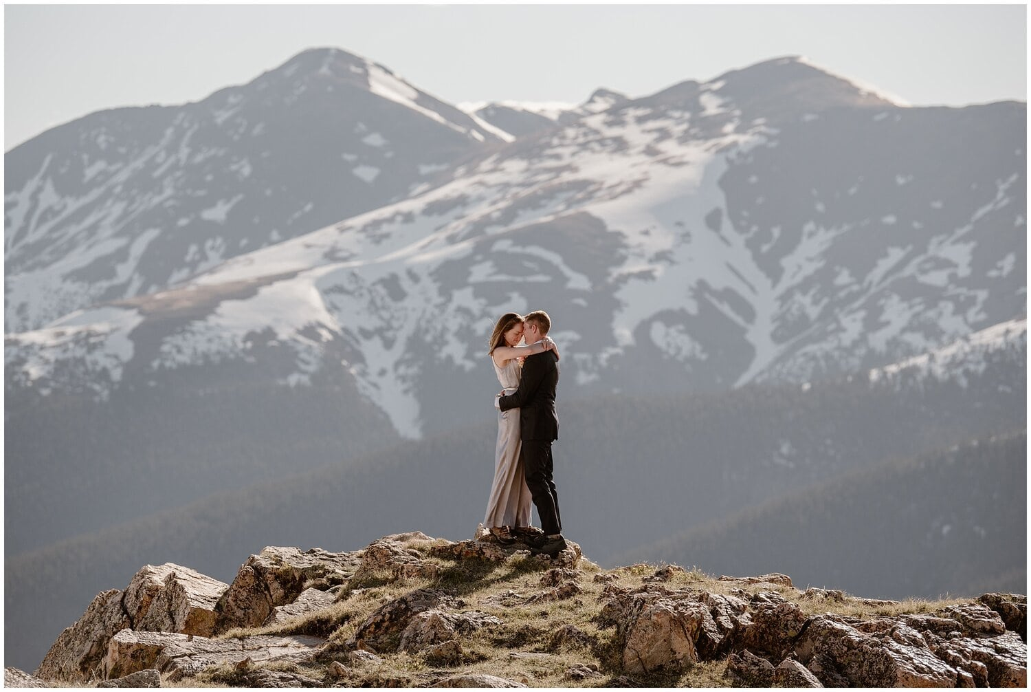 Bride and groom embrace on a mountain during their elopement.