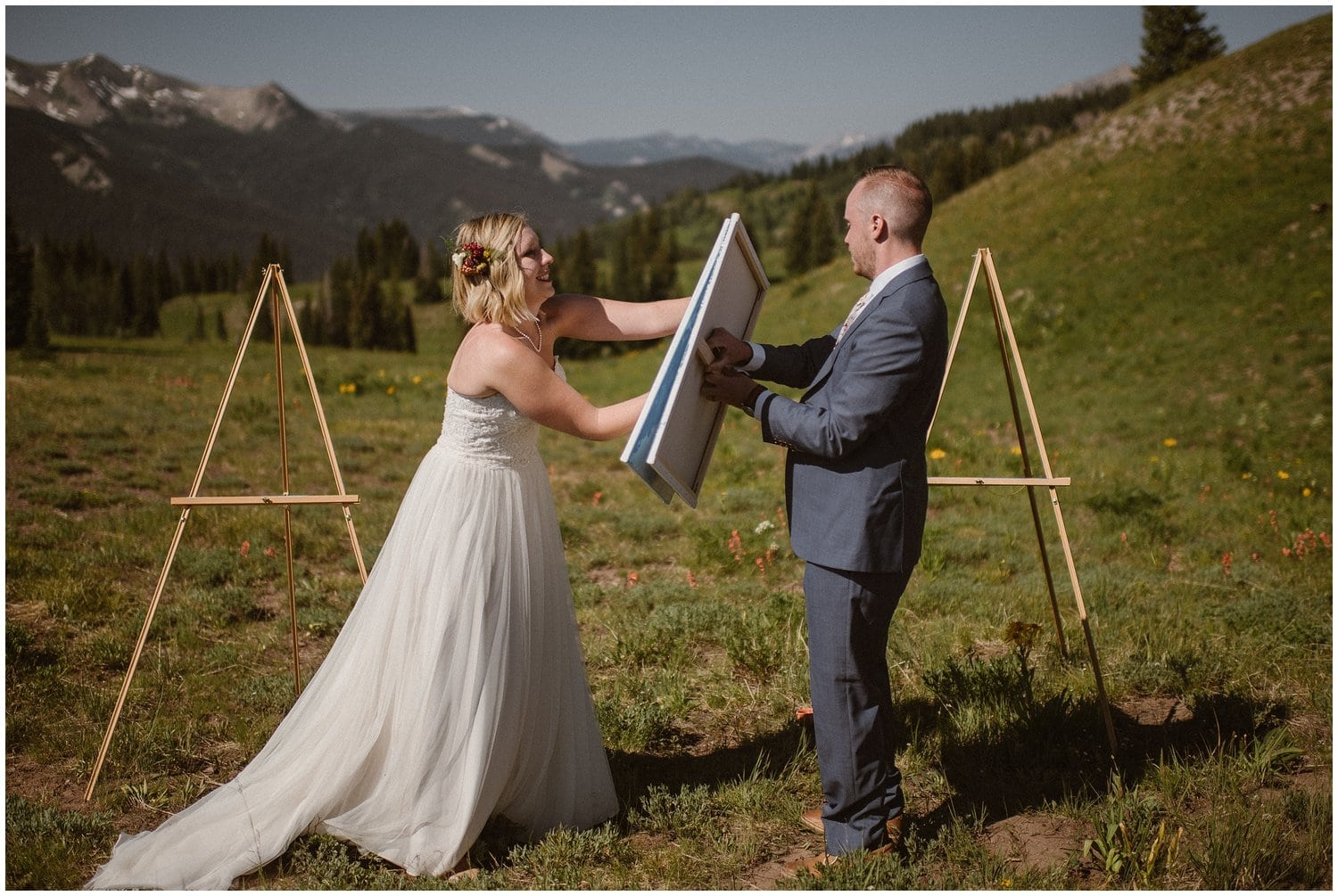 Bride and groom hold paint canvases toward each other during their adventure elopement.