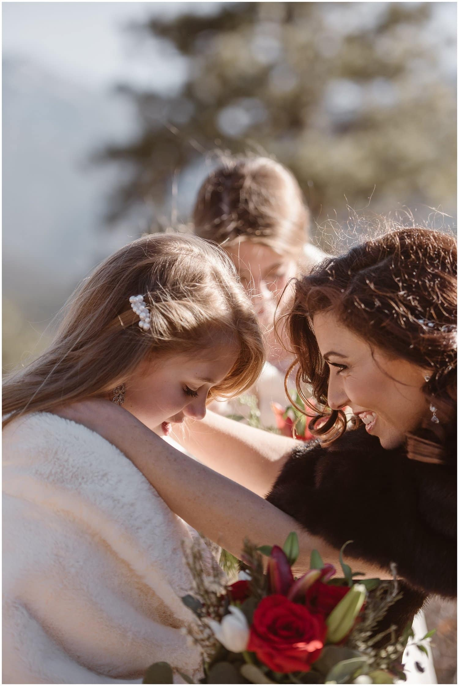 A bride smiles at her daughter on her wedding day.