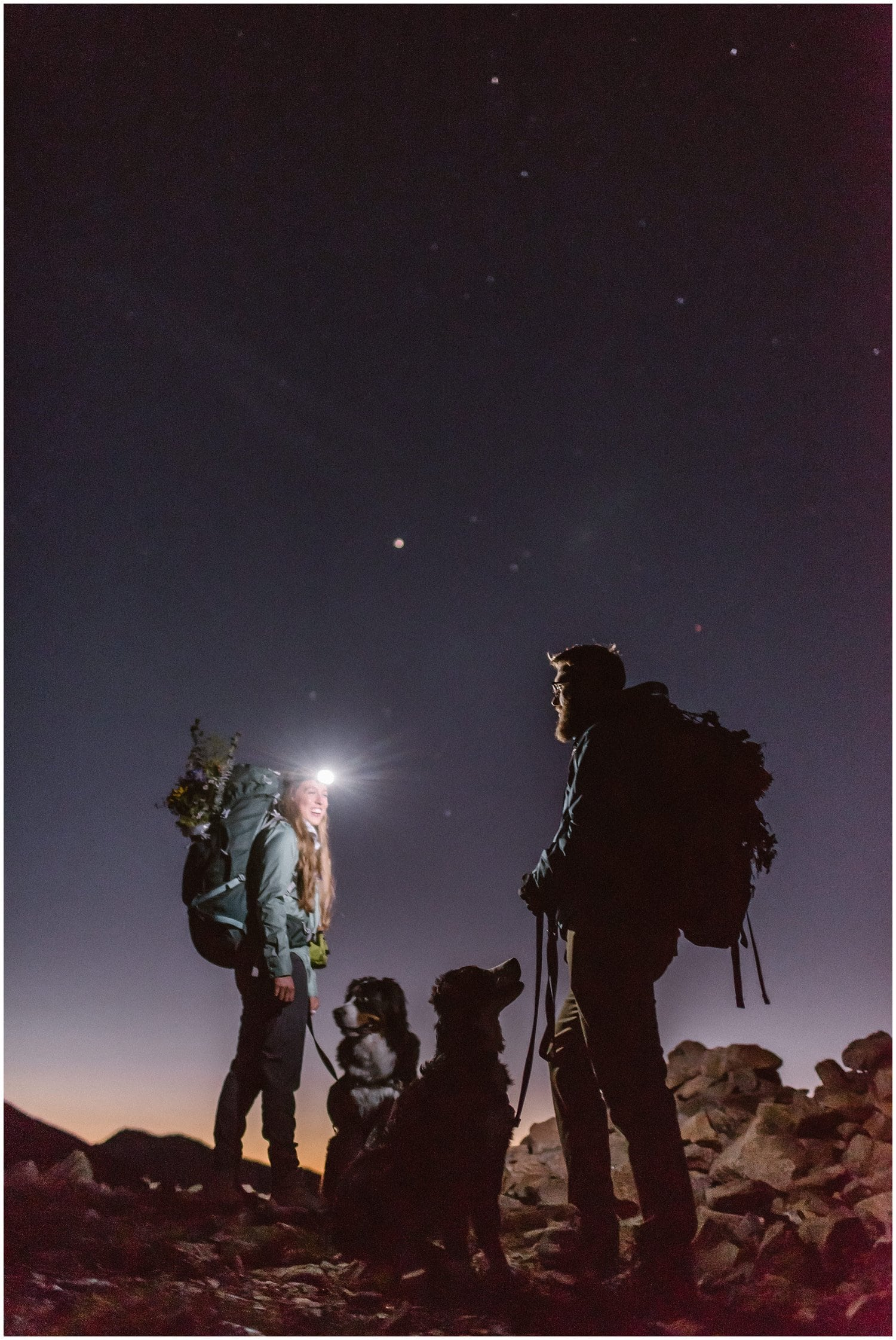 A woman and man smile at each other while hiking in the dark with their two dogs. The woman is wearing a headlight.