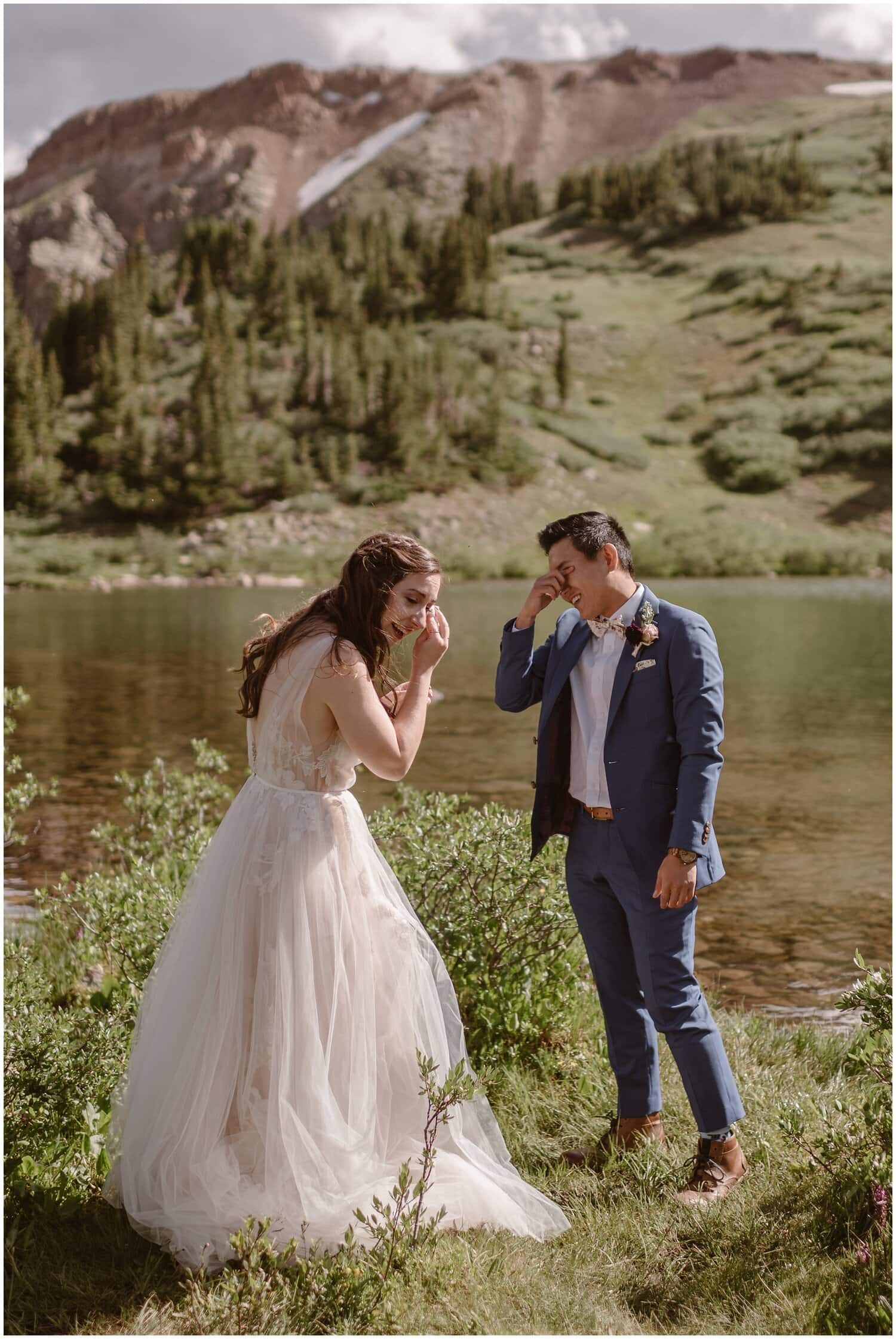 Bride and groom wipe tears off their eyes during their elopement.