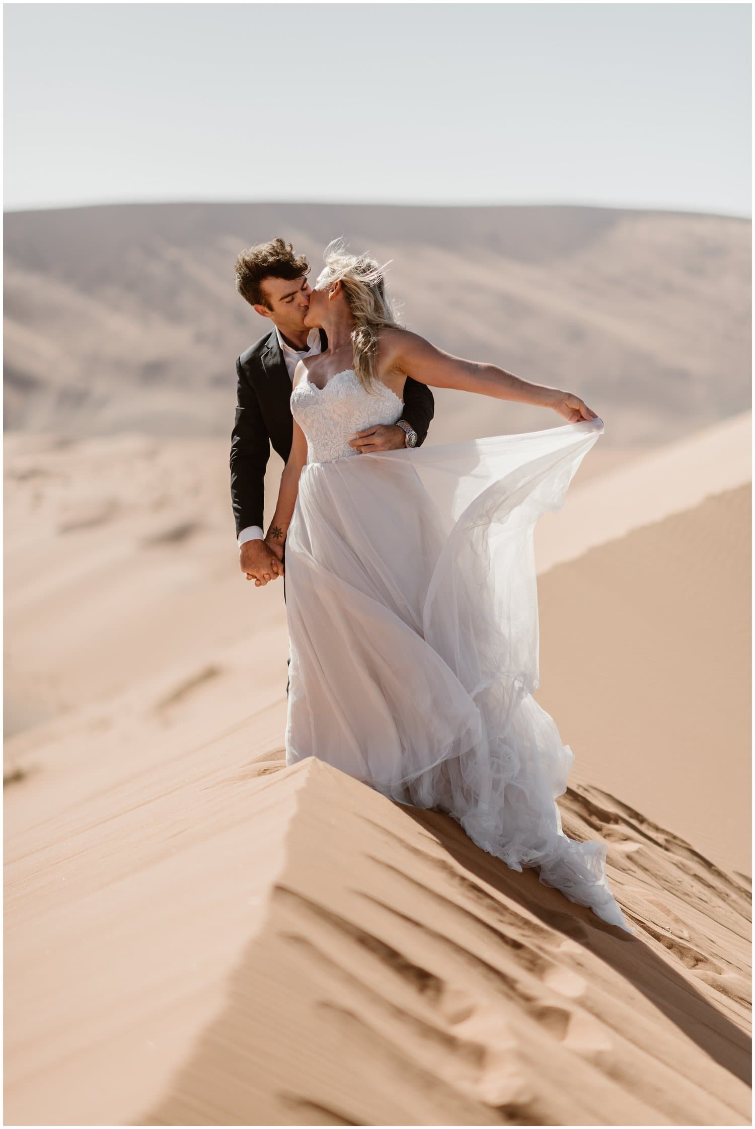 Bride and groom kiss in the desert on their wedding day.