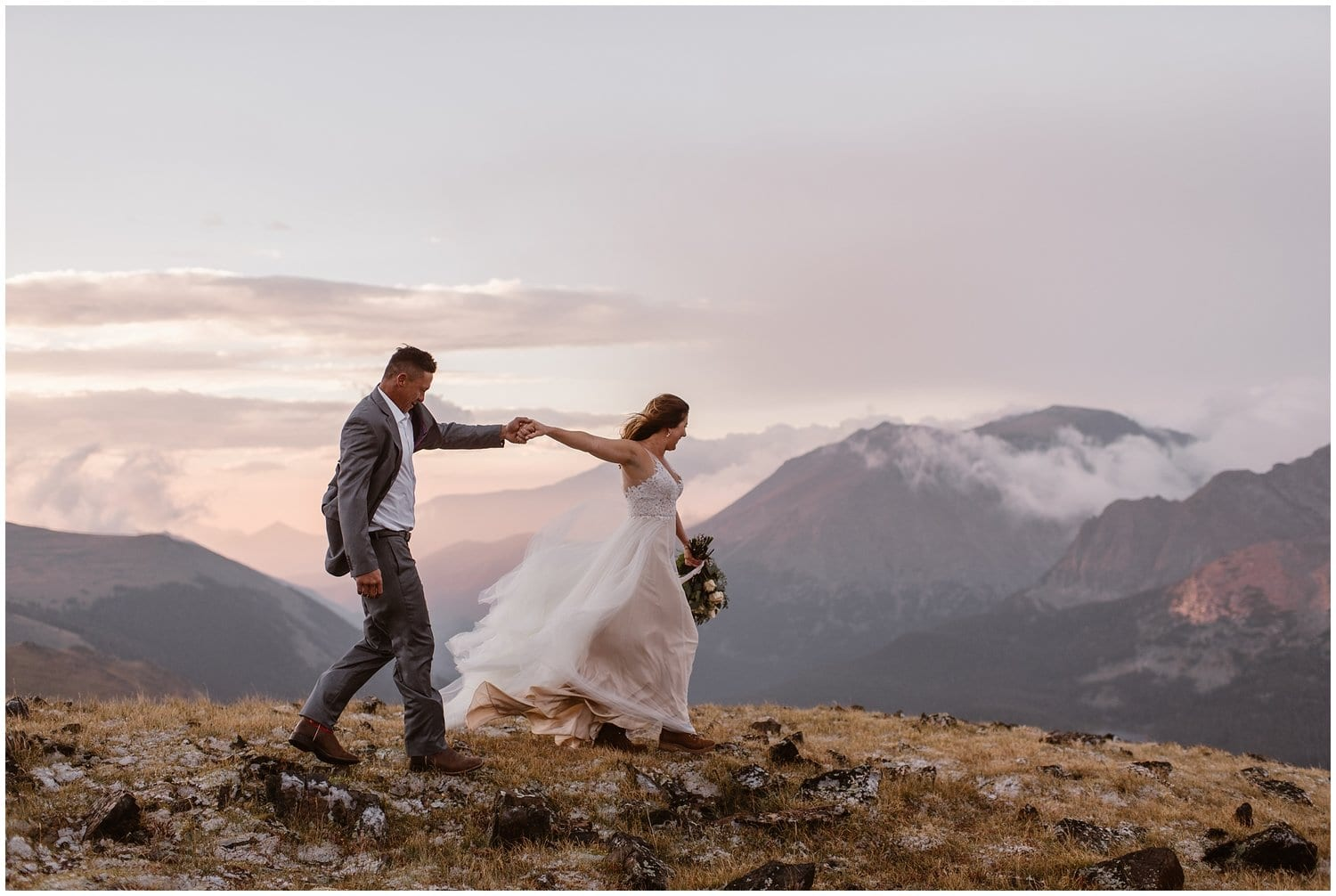 A bride and groom walk hand in hand in the mountains on their wedding day.