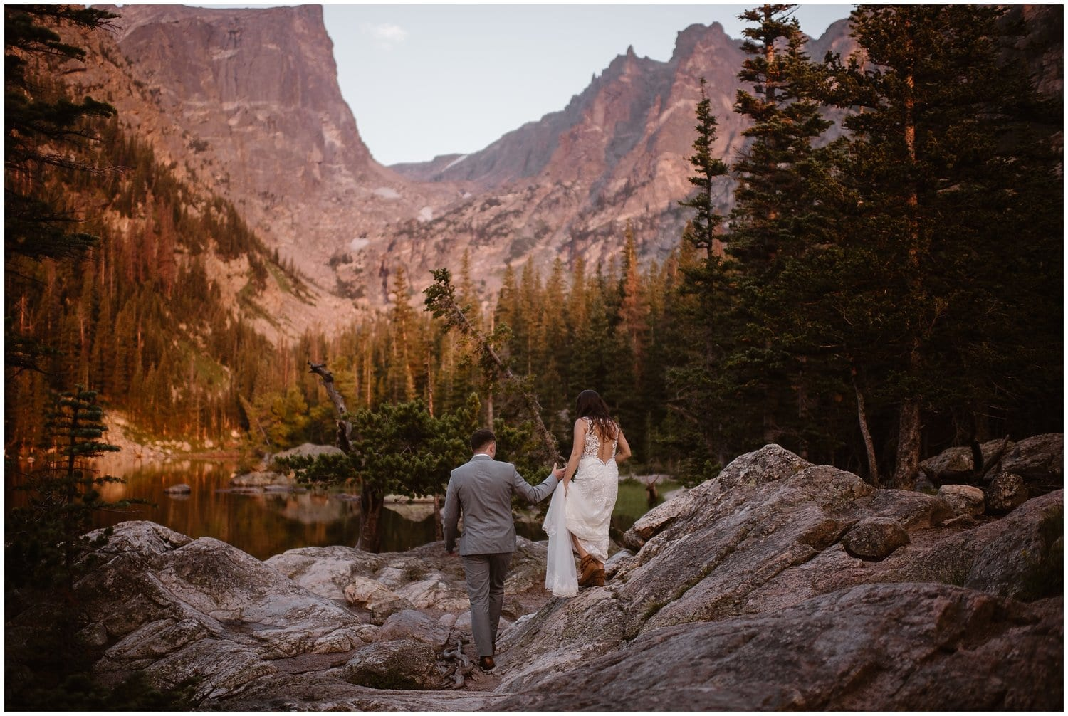 A bride and groom walk hand in hand in the forest on their wedding day.