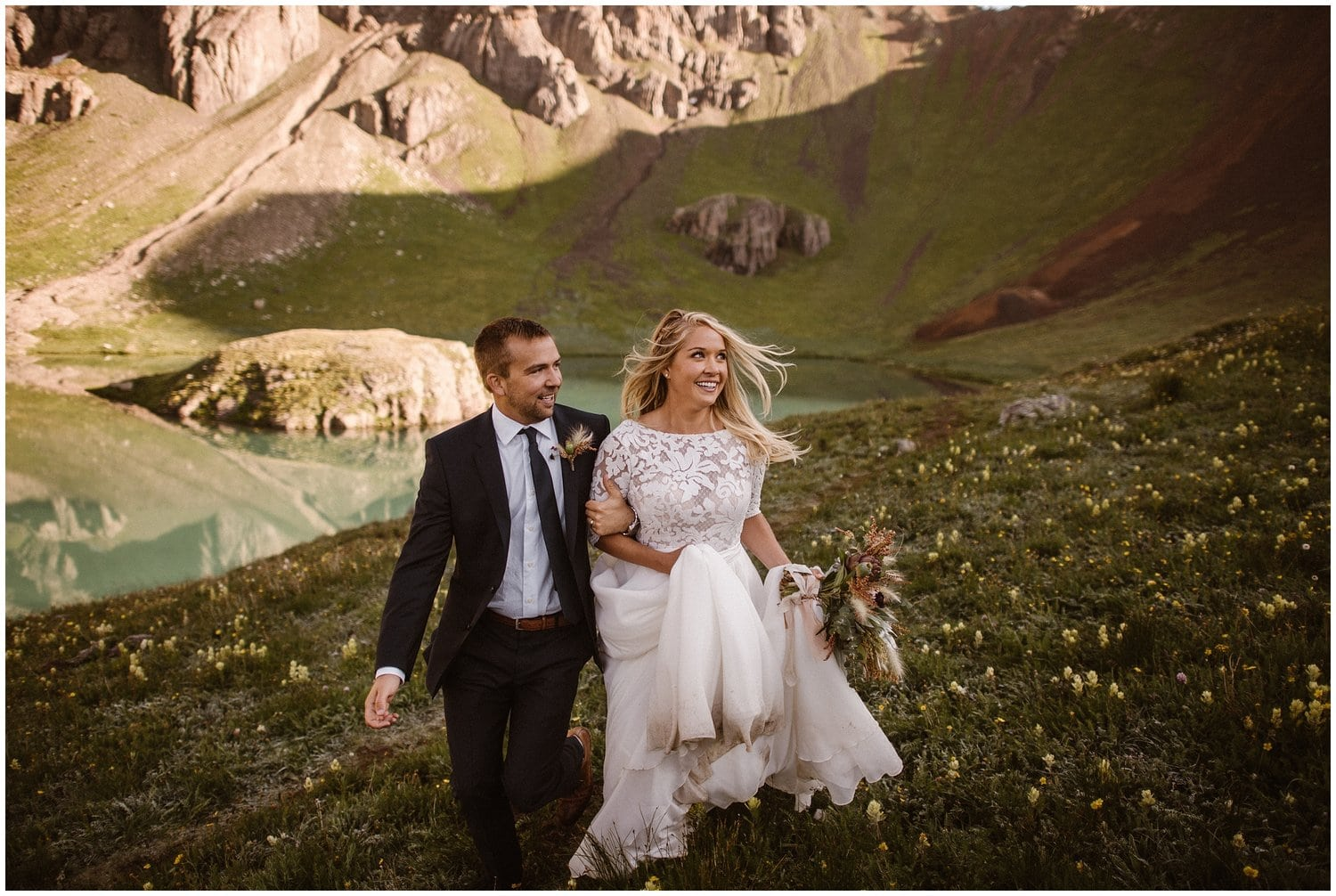 Bride and groom walk hand in hand in the San Juan Mountains on their wedding day.