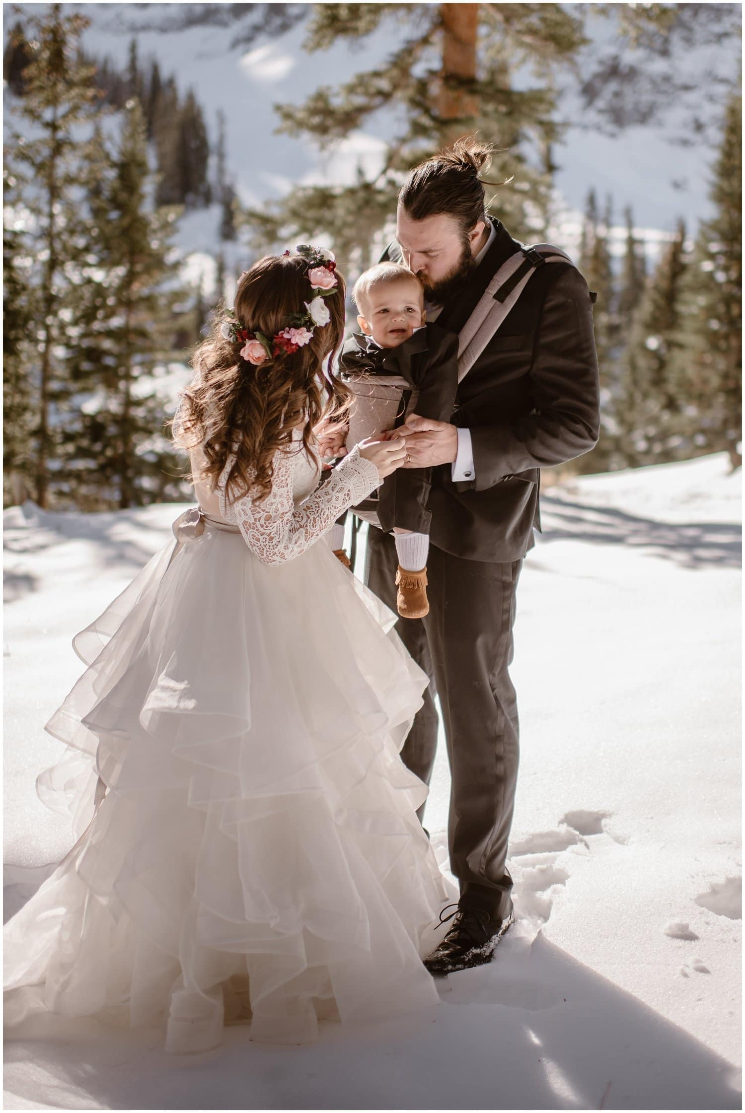 Bride and groom embrace their little baby in the mountains on their wedding day.