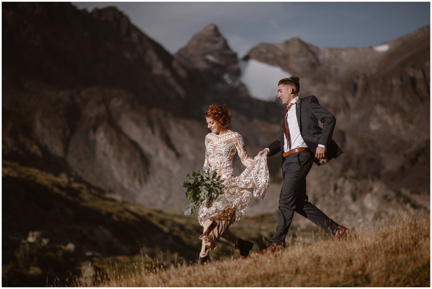 Groom helps bride hold her dress while walking down the mountain on their wedding day.