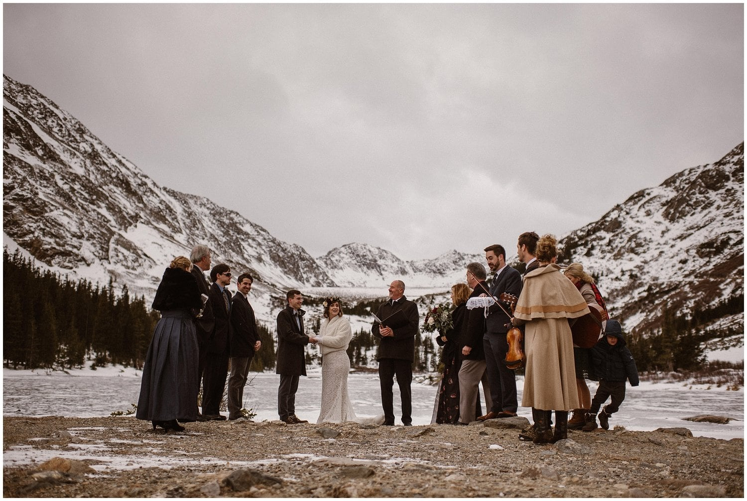A bride and groom have a wedding ceremony in the snowy mountains with family and friends standing by their side.
