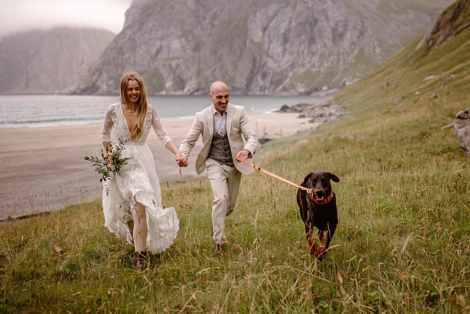 Bride and groom walk hand in hand with their dog on their wedding day in Norway.