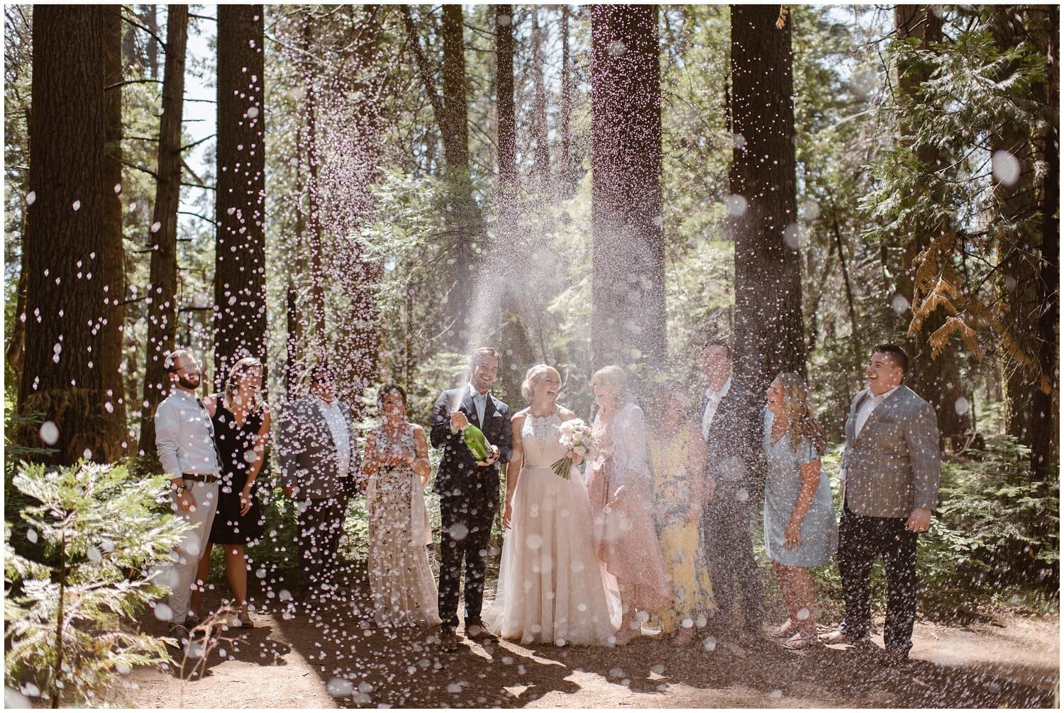 Bride and groom spray a bottle fo champagne with their friends and family on their wedding day.
