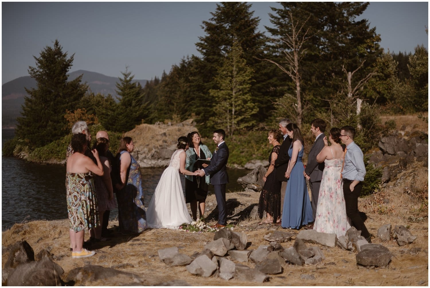 A bride and groom have an intimate ceremony by a body of water.