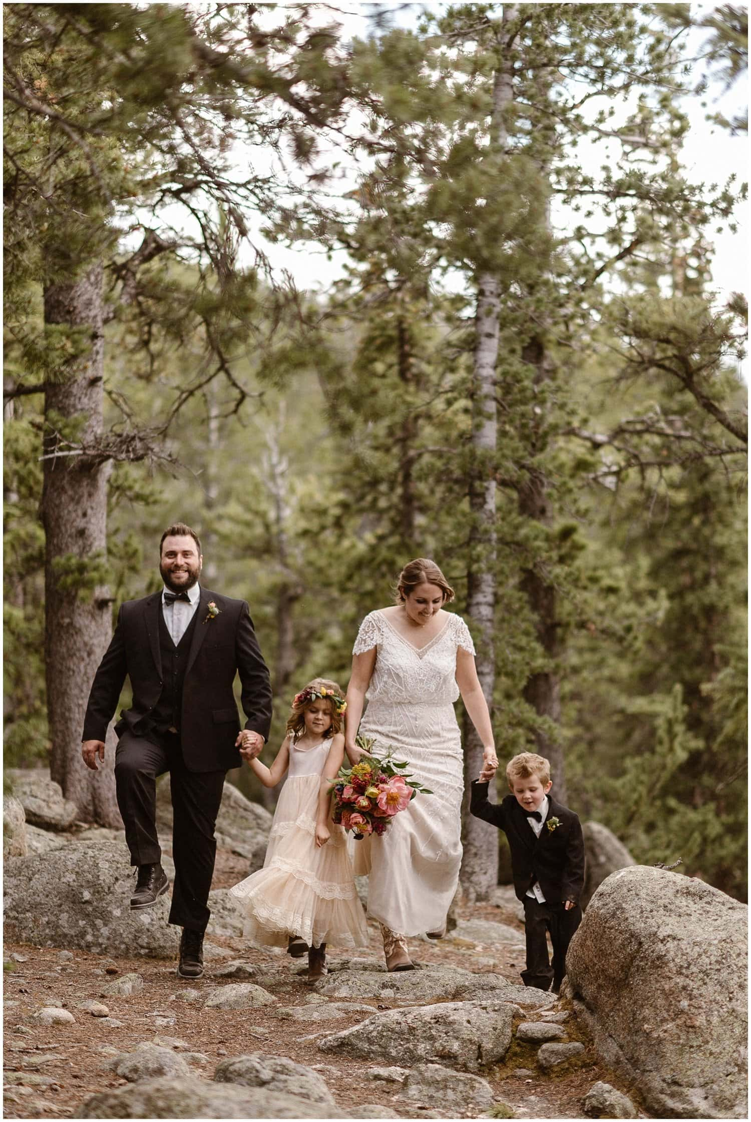 Bride and groom walk hand in hand with their two kids in the forest on their wedding day.