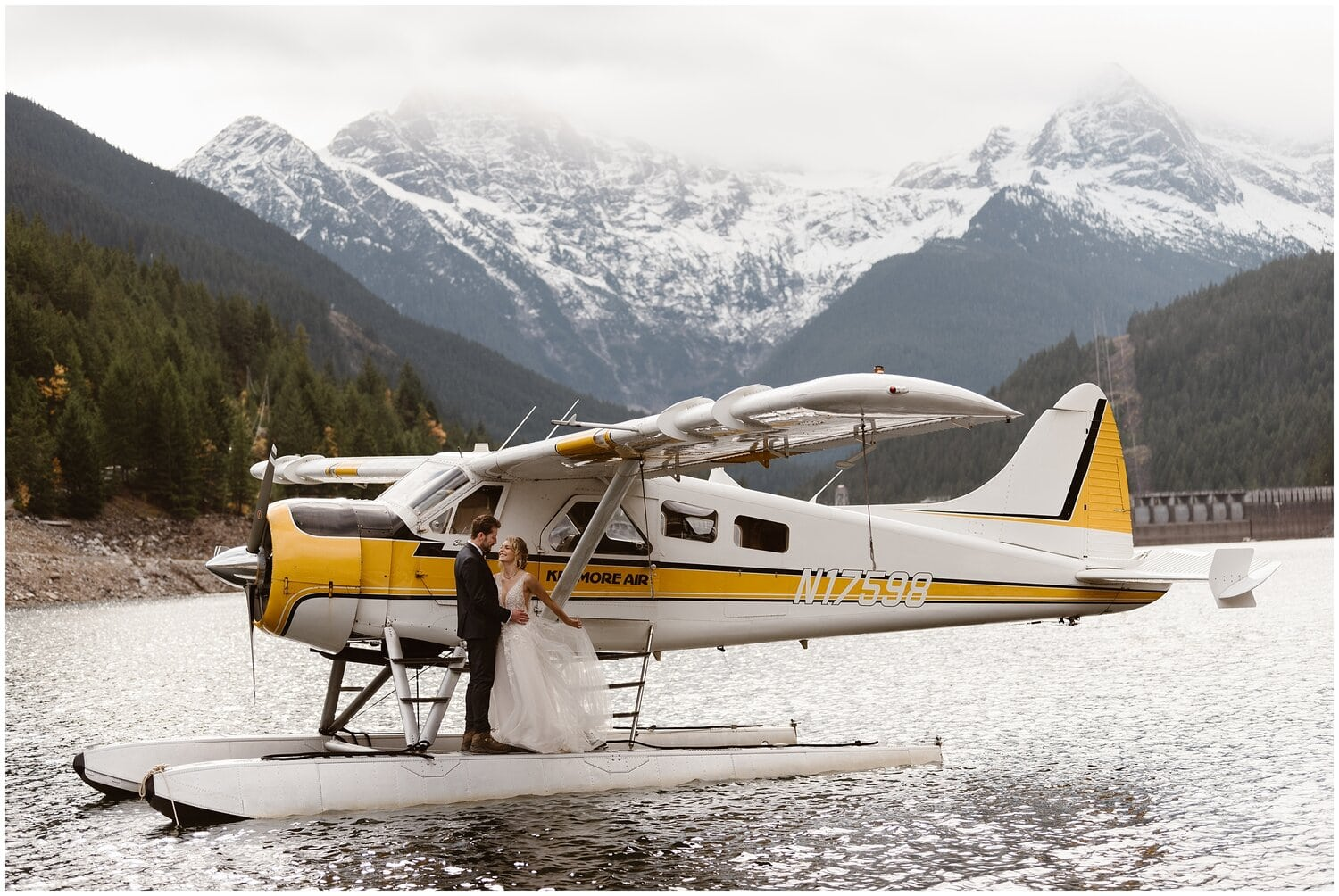 Bride and groom stand in front of a helicopter on their wedding day.