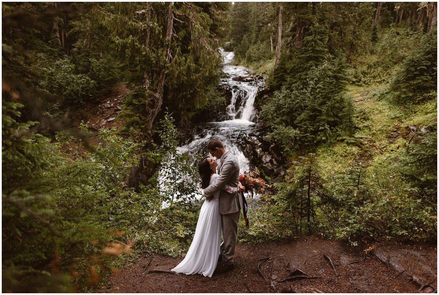 A bride and groom embrace near a waterfall on their wedding day.