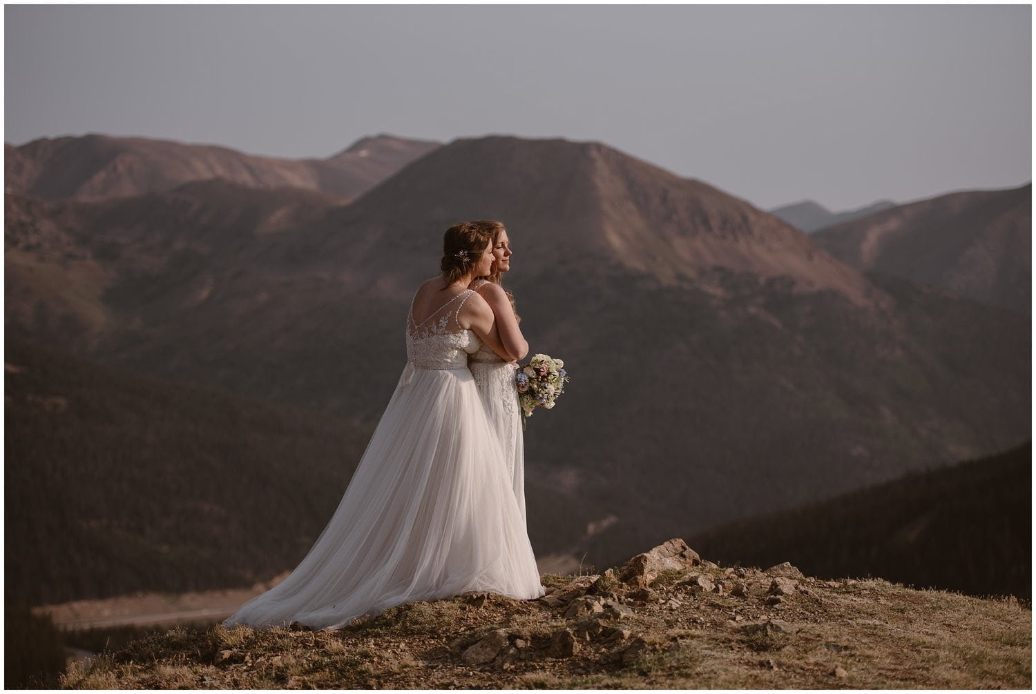A couple embrace in the mountains on their wedding day.