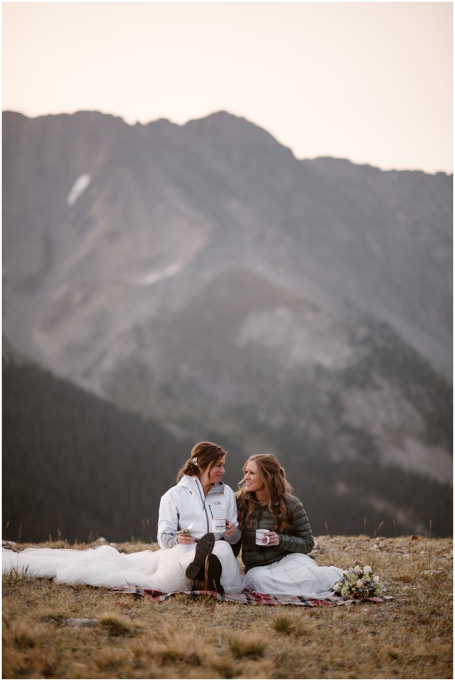Two brides wearing winter jackets have a picnic on a mountain on their wedding day.