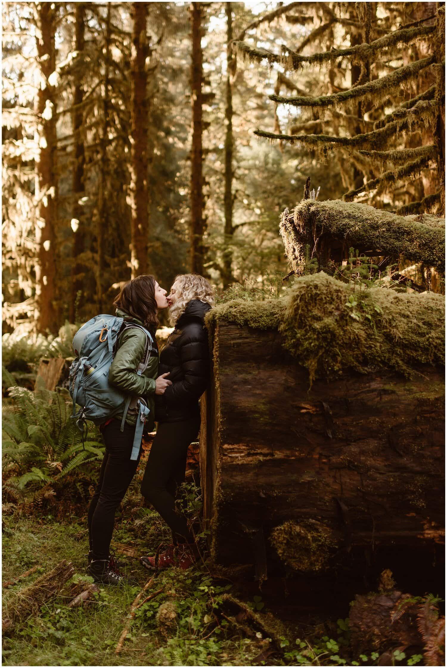 Two brides kiss in a forest while dressed in hiking gear.