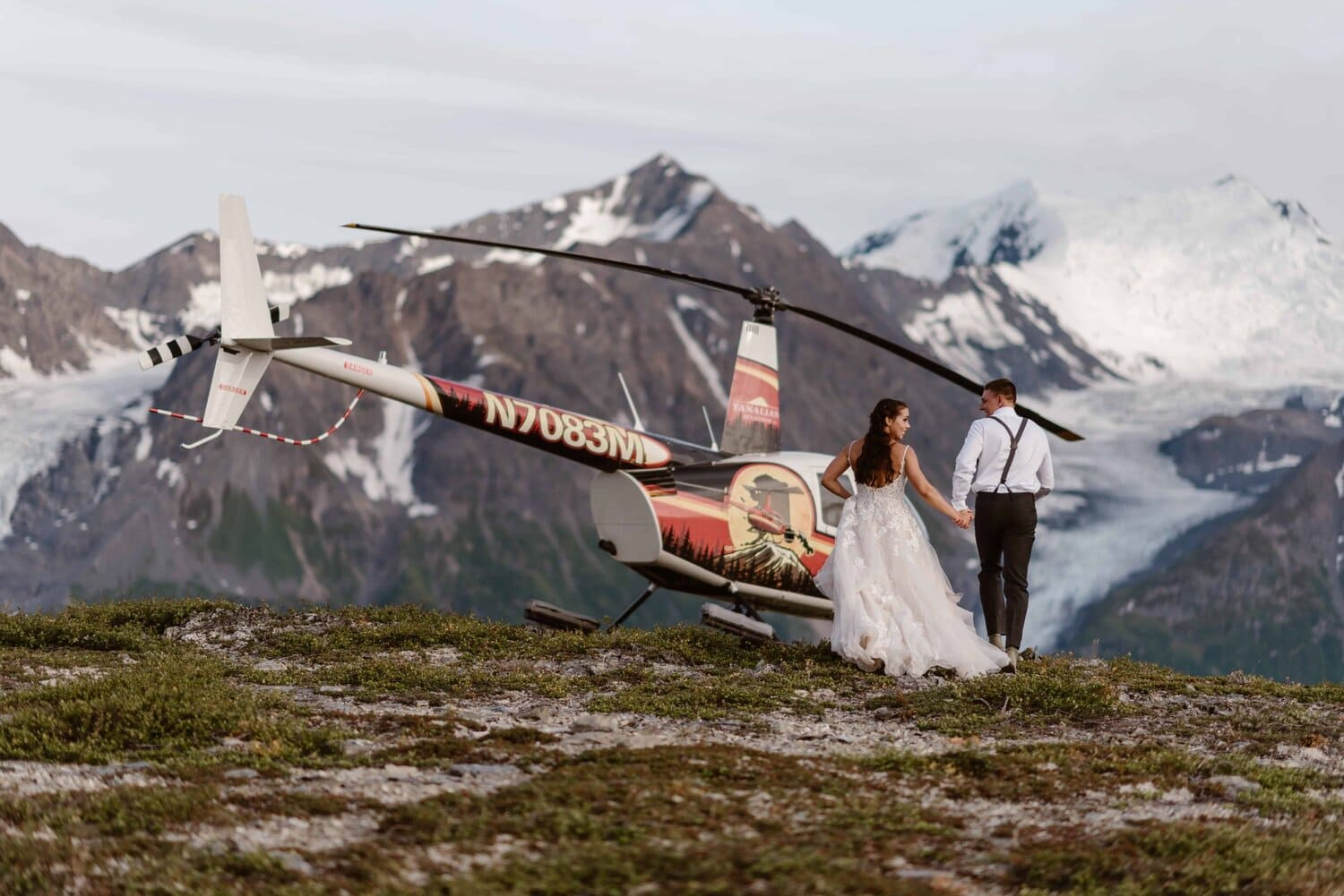 Bride and groom hold hands while walking towards a helicopter.