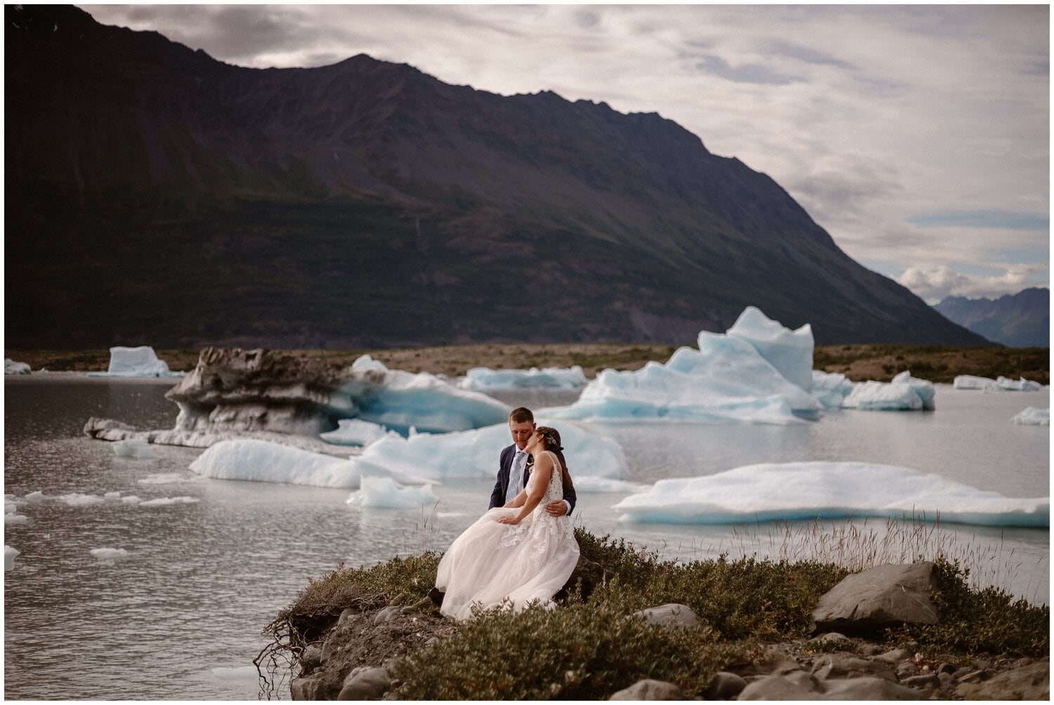 Bride and groom sit near a body of water with glaciers floating on their wedding day.