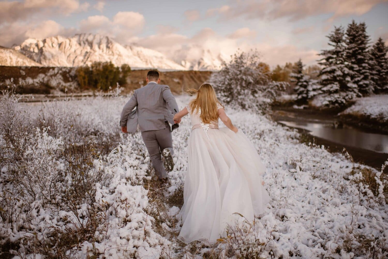 Bride and groom walk through the snow.
