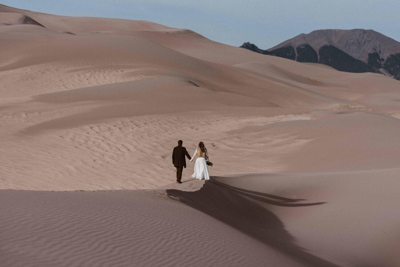 Bride and groom walk across the sand dunes.