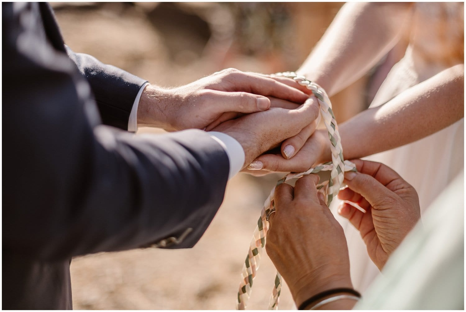Close-up of rope being tied around bride and groom's hands during their elopement ceremony.