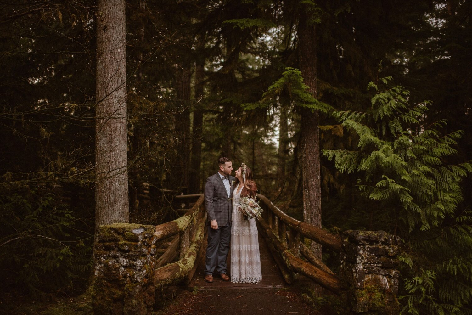 A bride and groom look at each other while standing on a bridge in the forest.