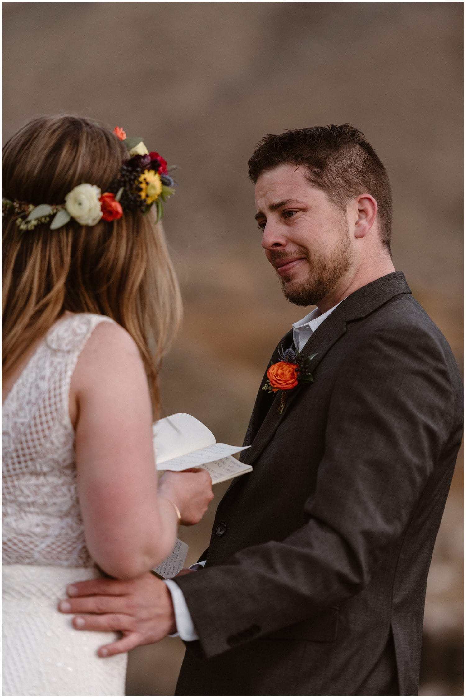 A groom is almost in tears as he looks as his bride reading her vows to him.