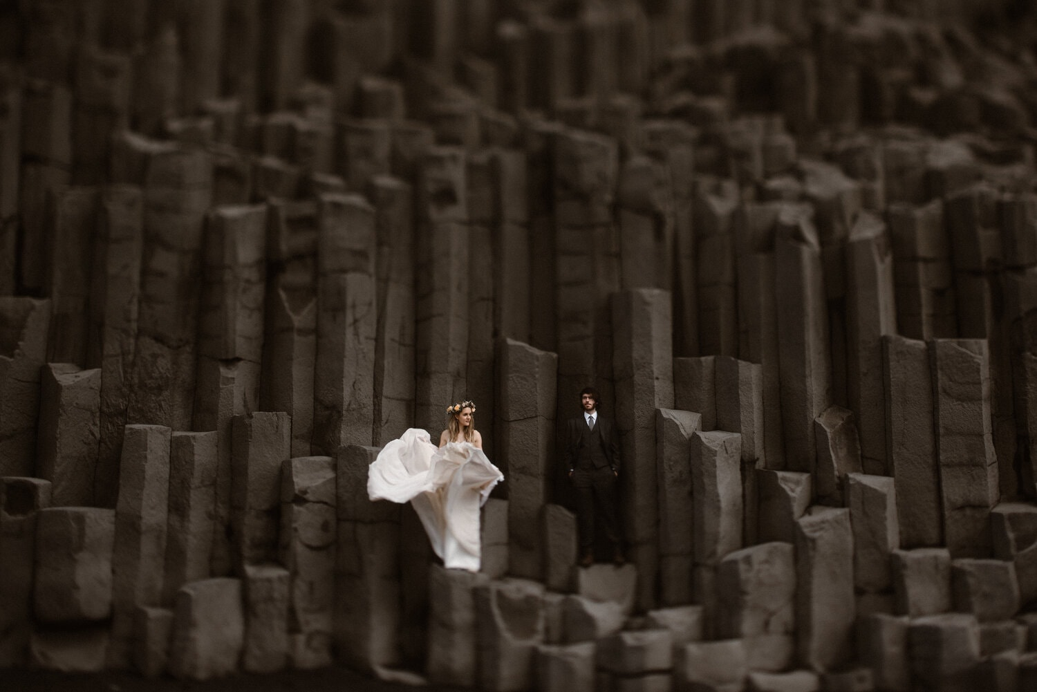 Bride and groom stand on dark gray rocks on their wedding day.
