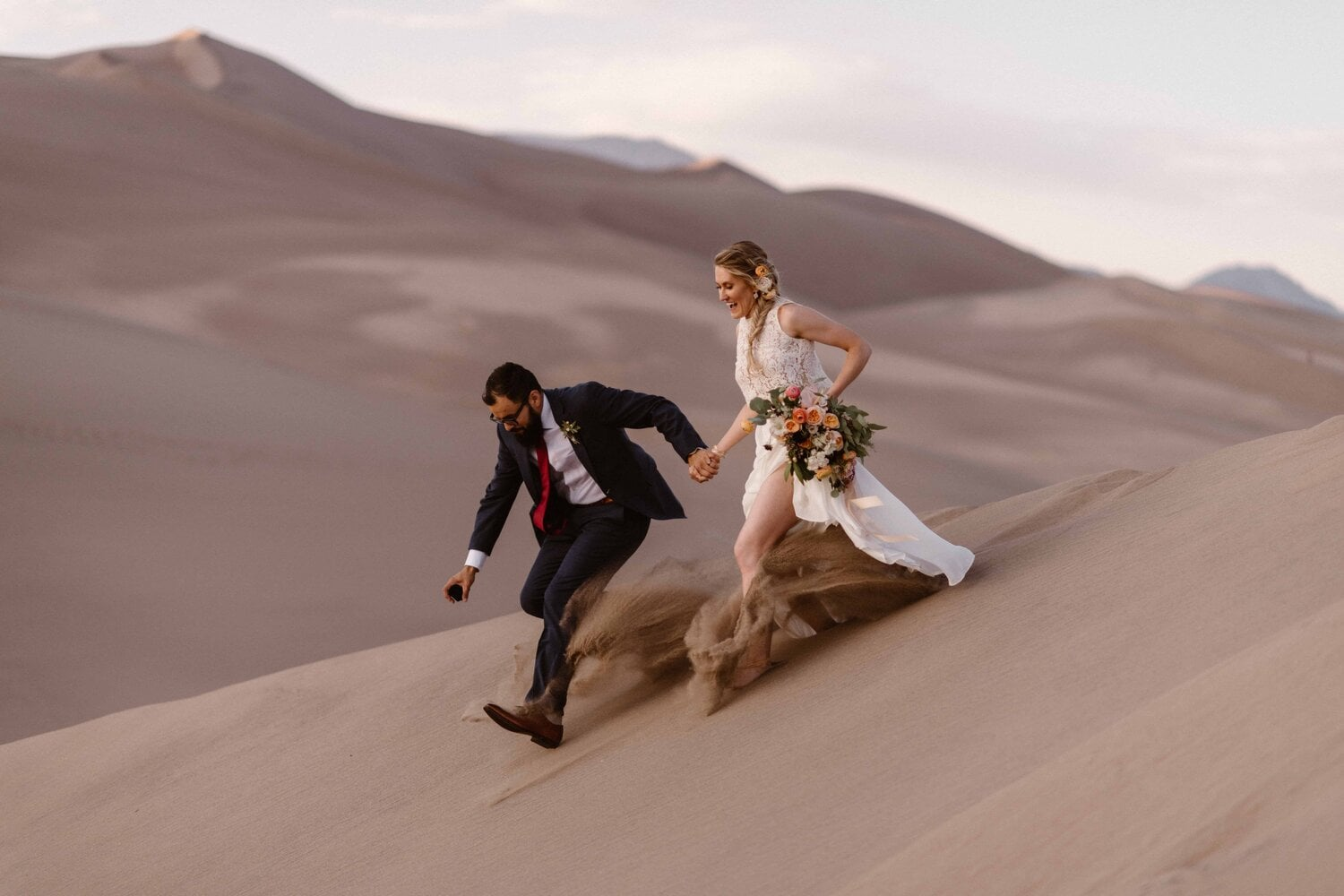 A bride and groom run down a sand dune hill.