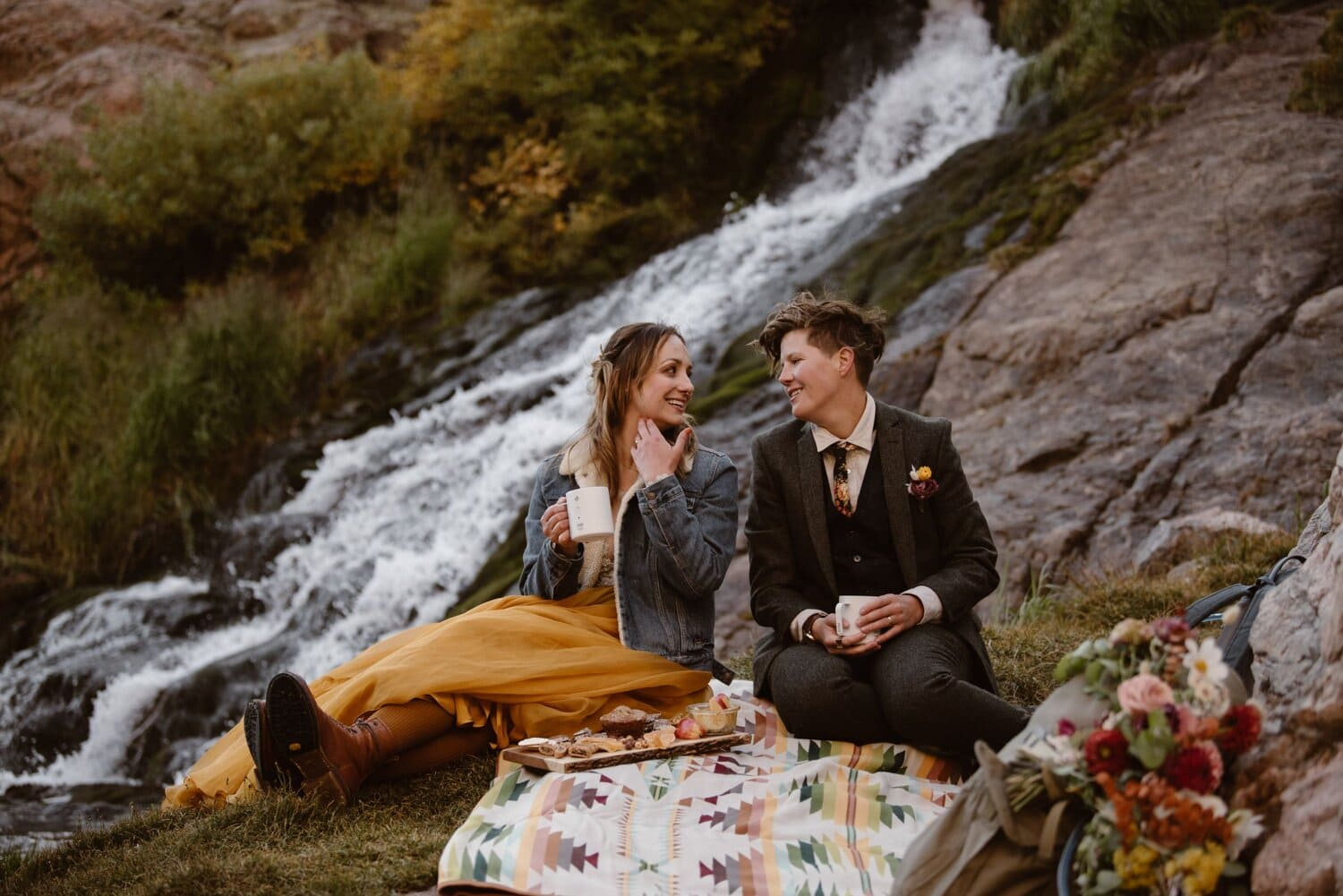 Two brides smile at each other while having a picnic near the waterfall on their elopement day.