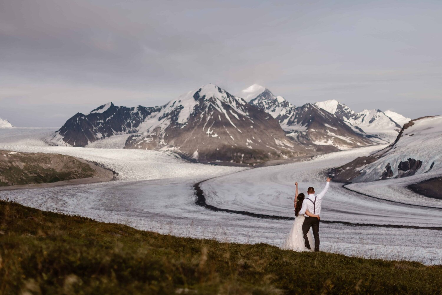 Bride and groom raise their hands while looking at the snowy mountains.