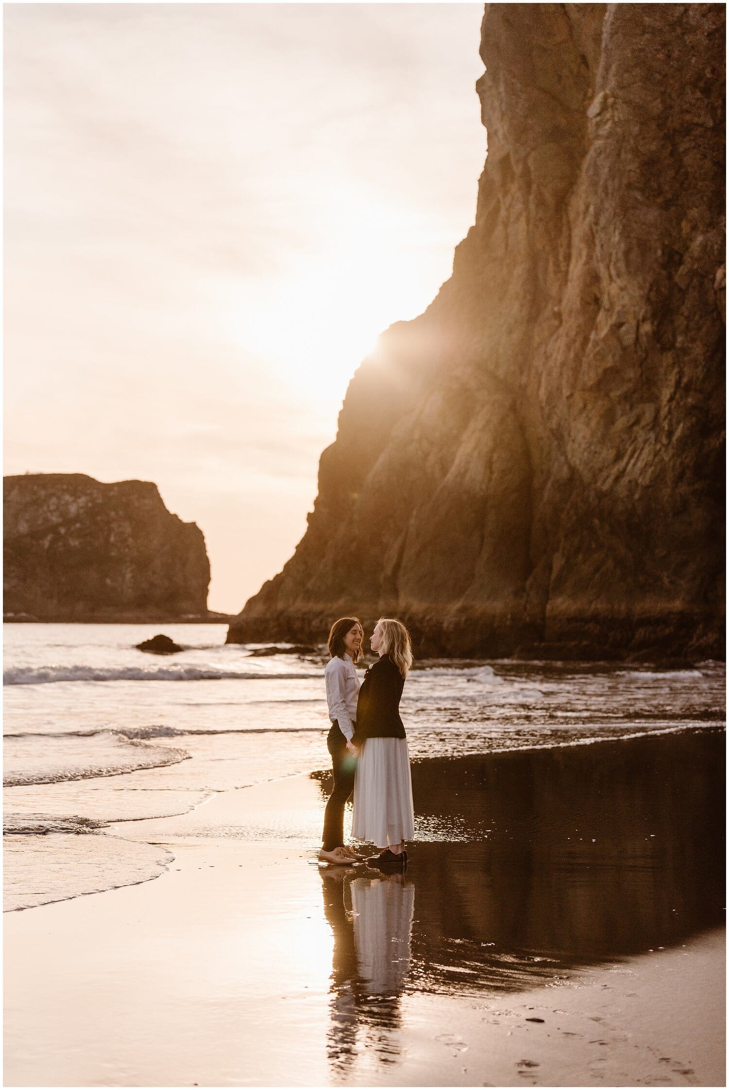 A couple stands on the shore of the beach on their wedding day.