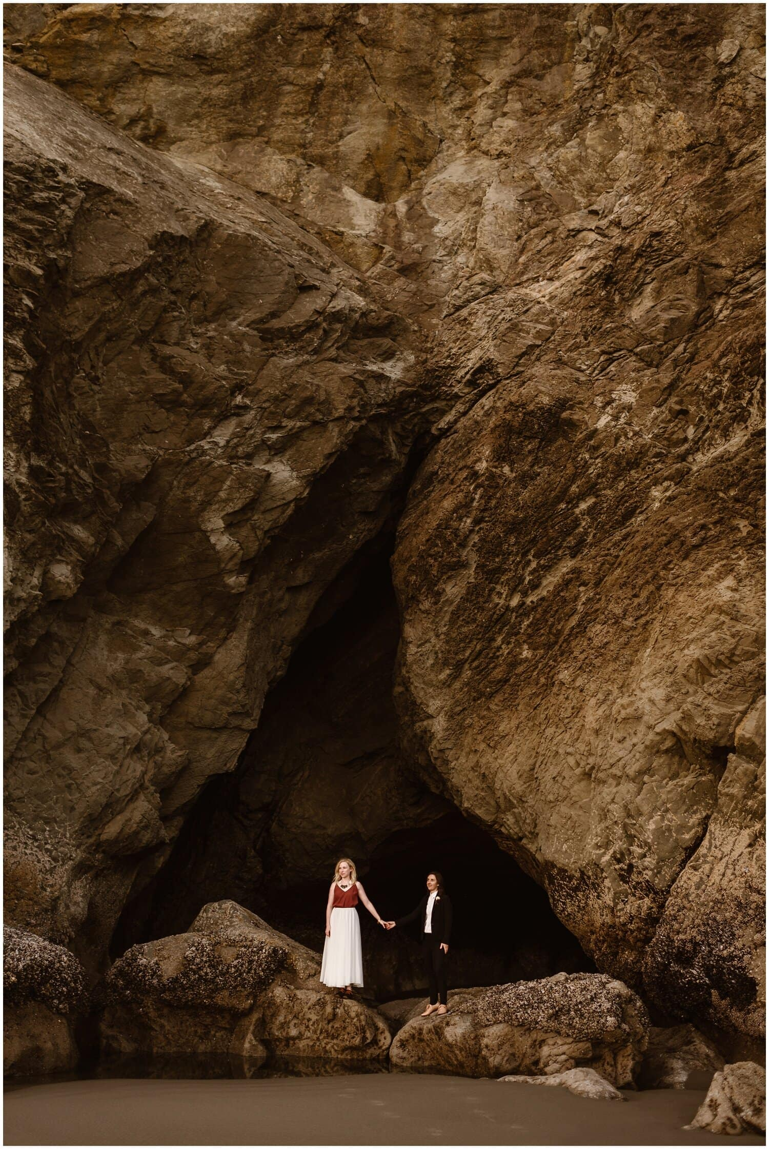 A couple stand on rocks by the beach on their elopement day.