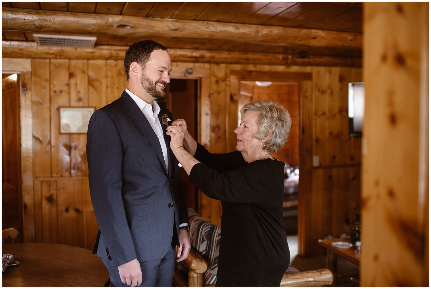 A groom smiles while a woman helps him pin a boutonnière on his jacket in a cabin.