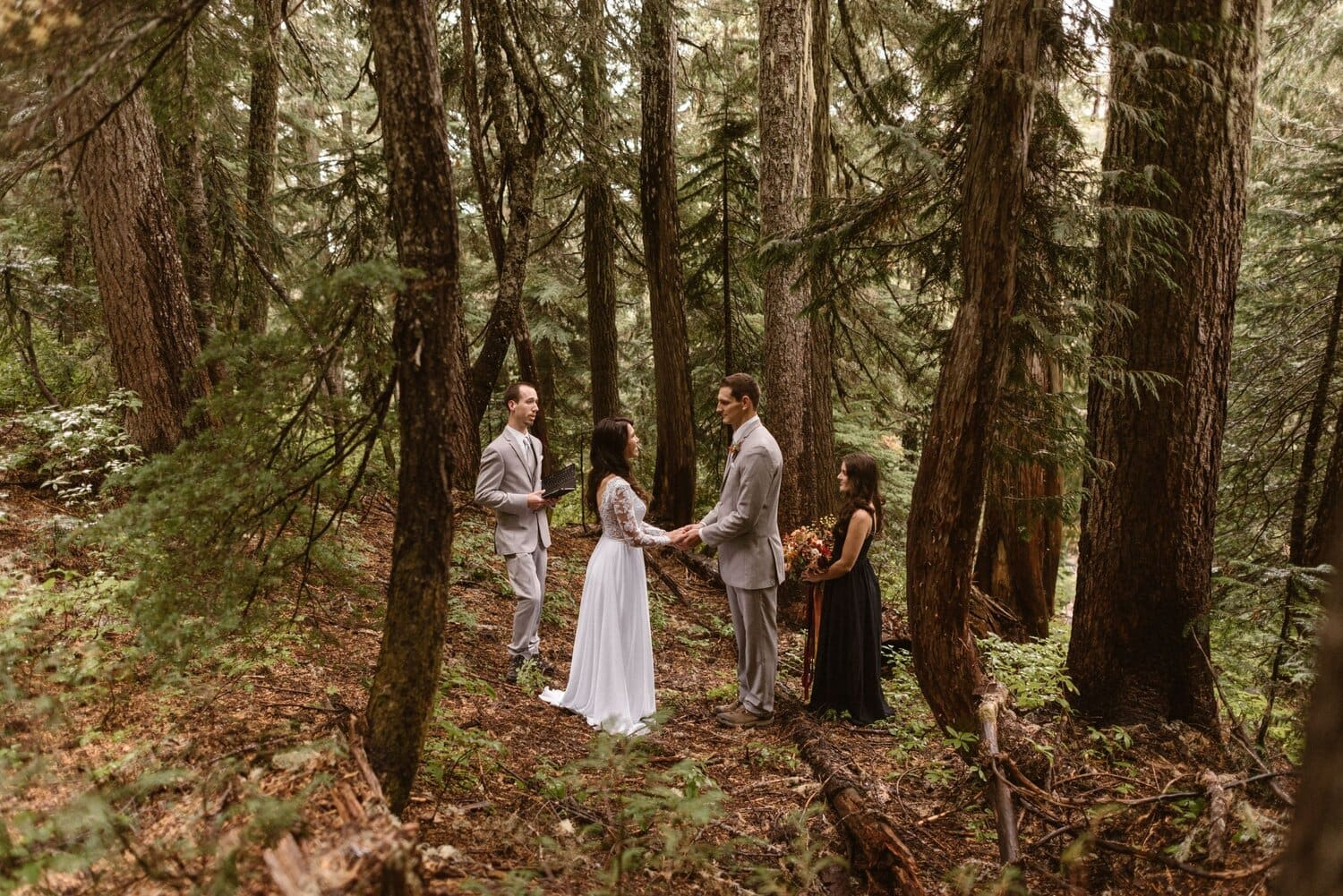 Bride and groom hold hands during their elopement ceremony while a man and woman stand on either side.