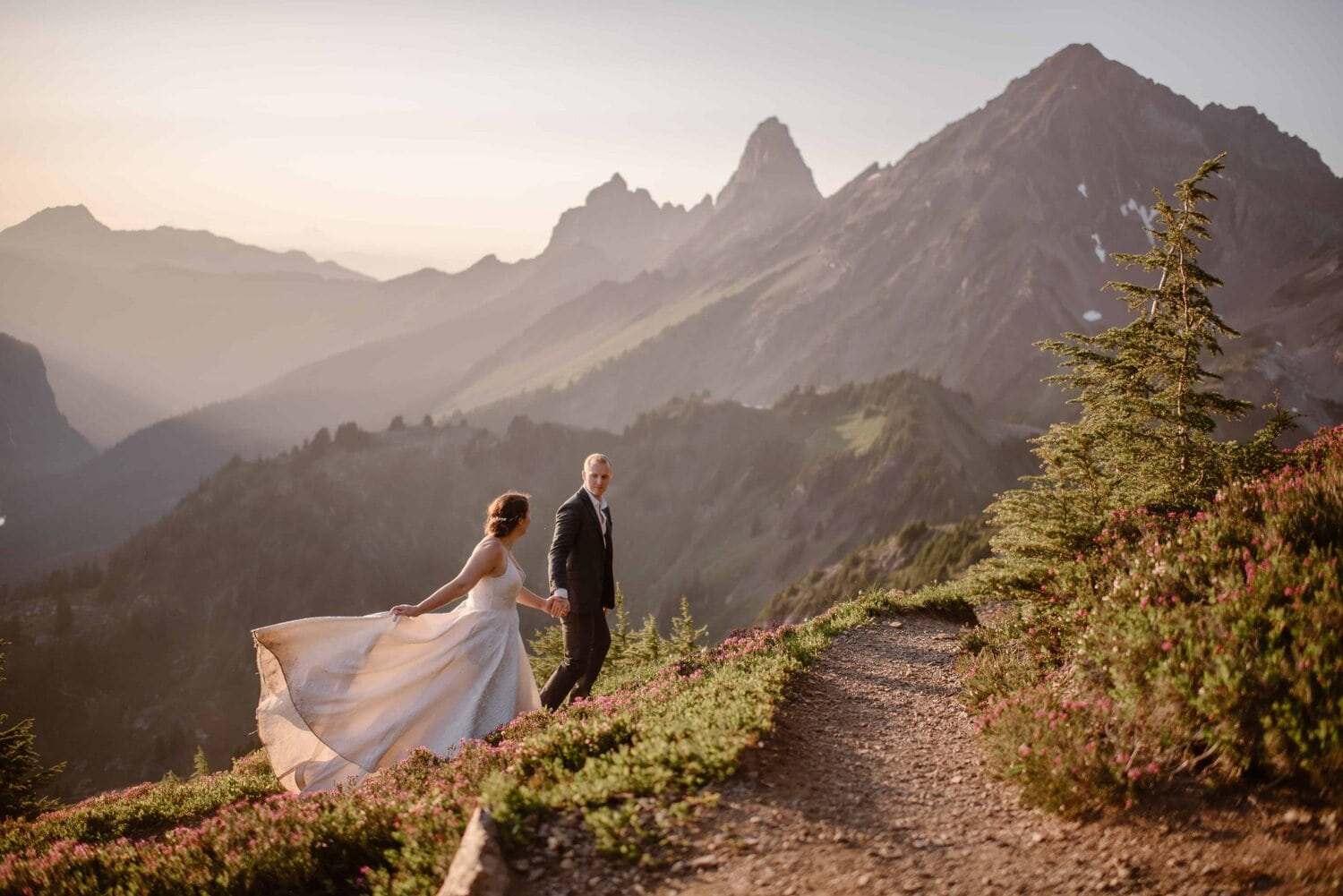 Bride and groom hold hands while walking up the mountains.