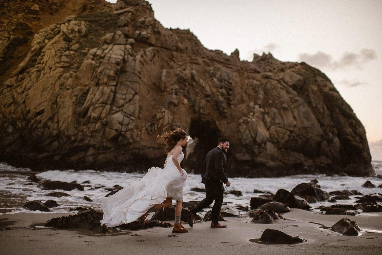 Bride and groom run across the coast.