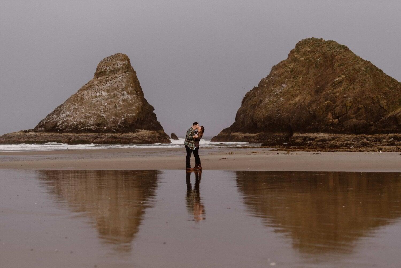 A couple kiss on a beach at the Oregon Coast.
