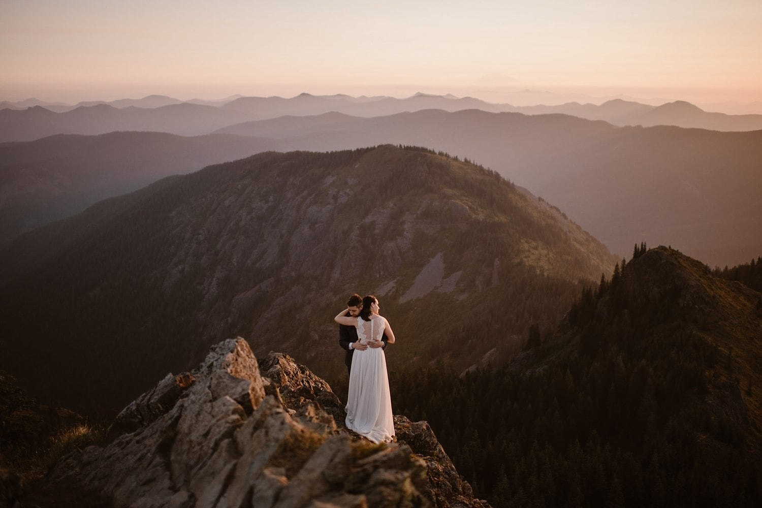 Bride and groom embrace on top of a mountain during their adventure elopement.