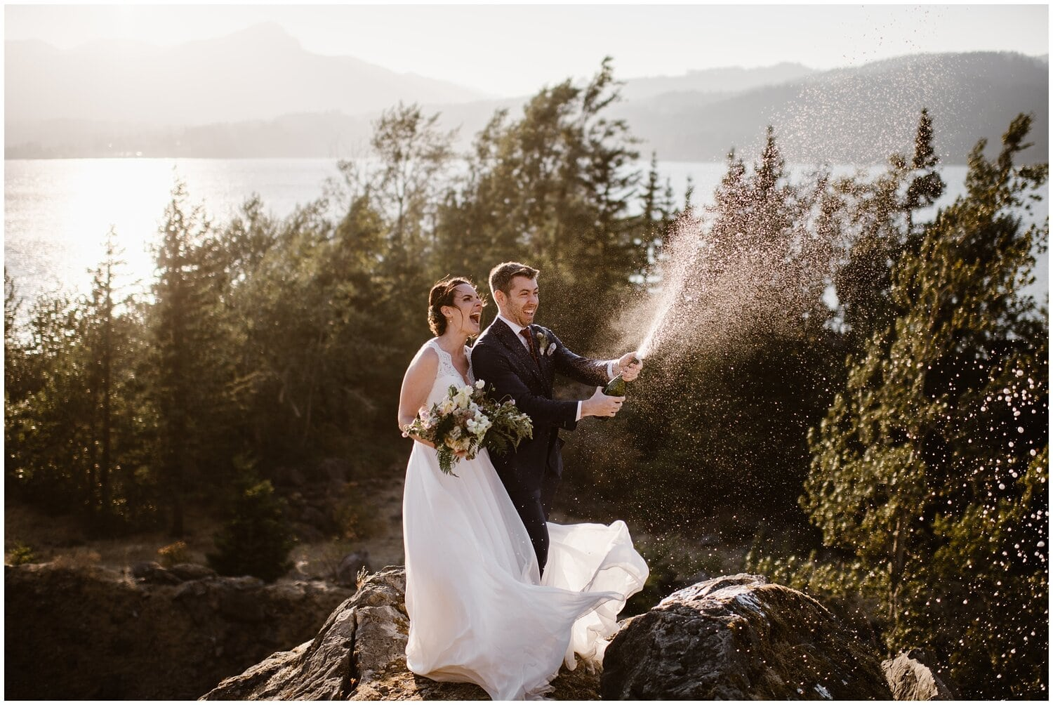 A bride and groom laugh while popping a bottle of champagne.