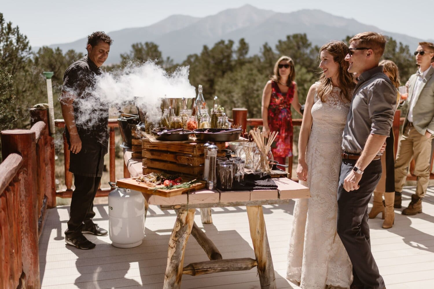 Bride and groom smile while standing in front of a food table on their elopement day.