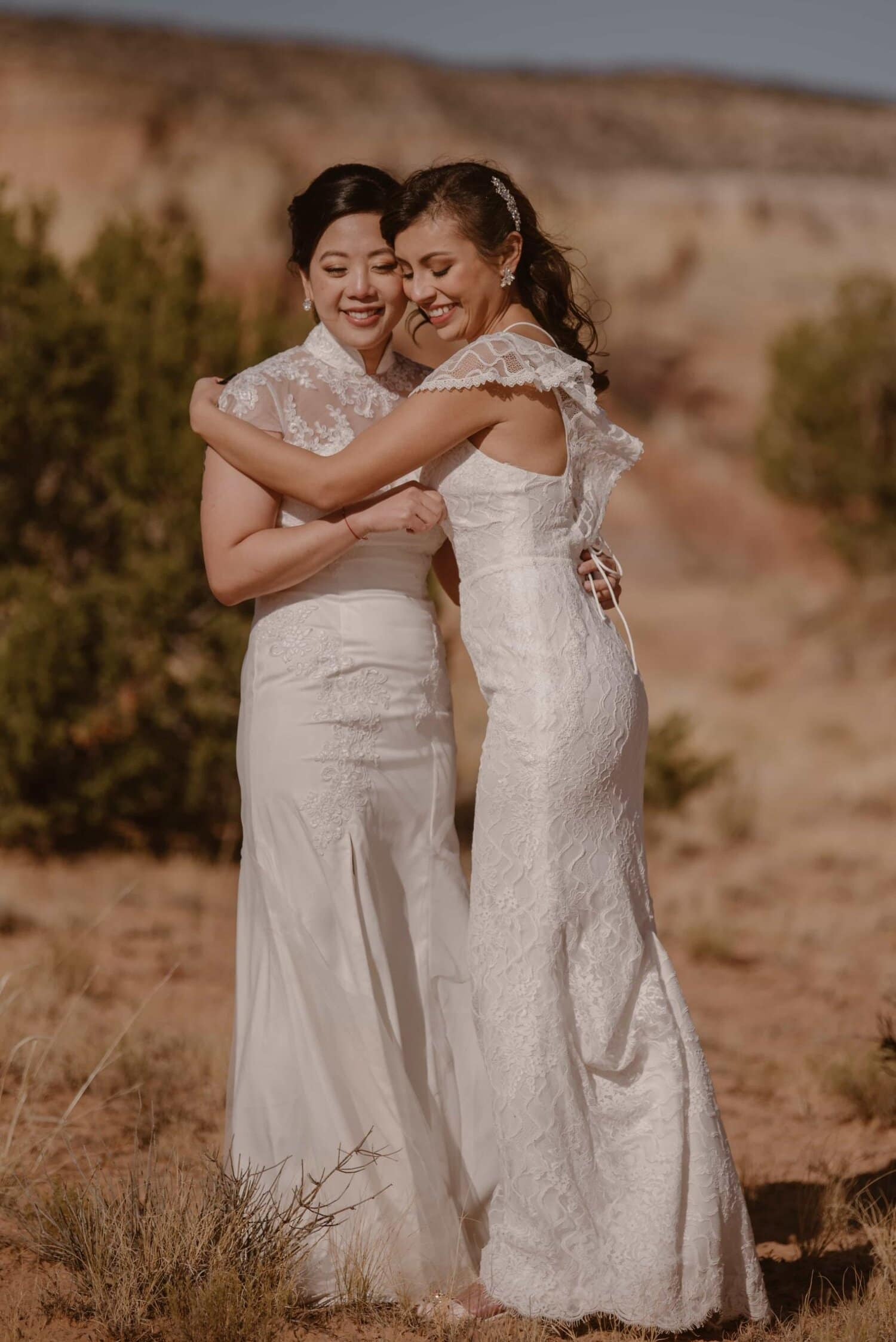 Two brides embrace on their wedding day.