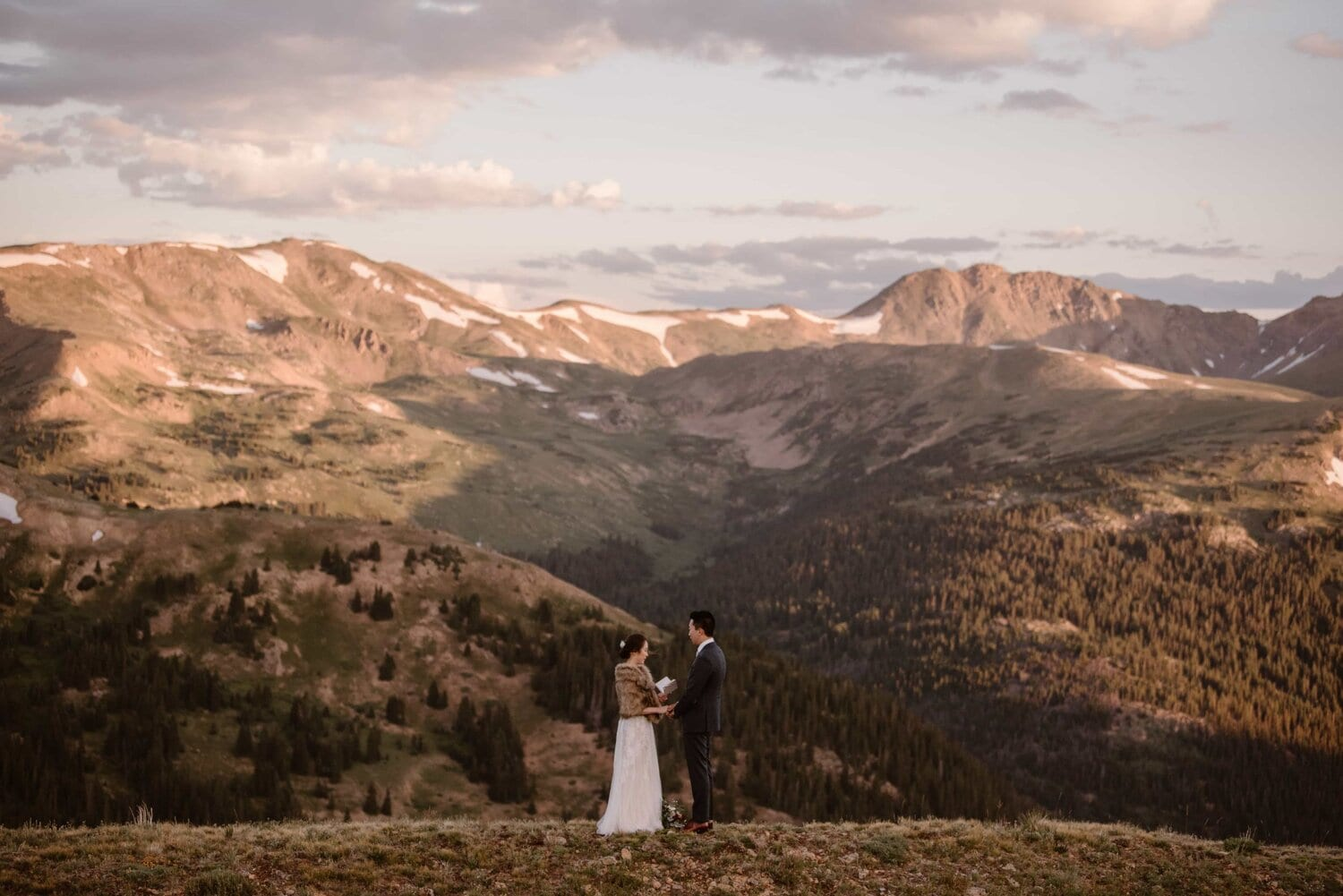 Bride and groom exchange vows on top of a mountain during their wedding ceremony.